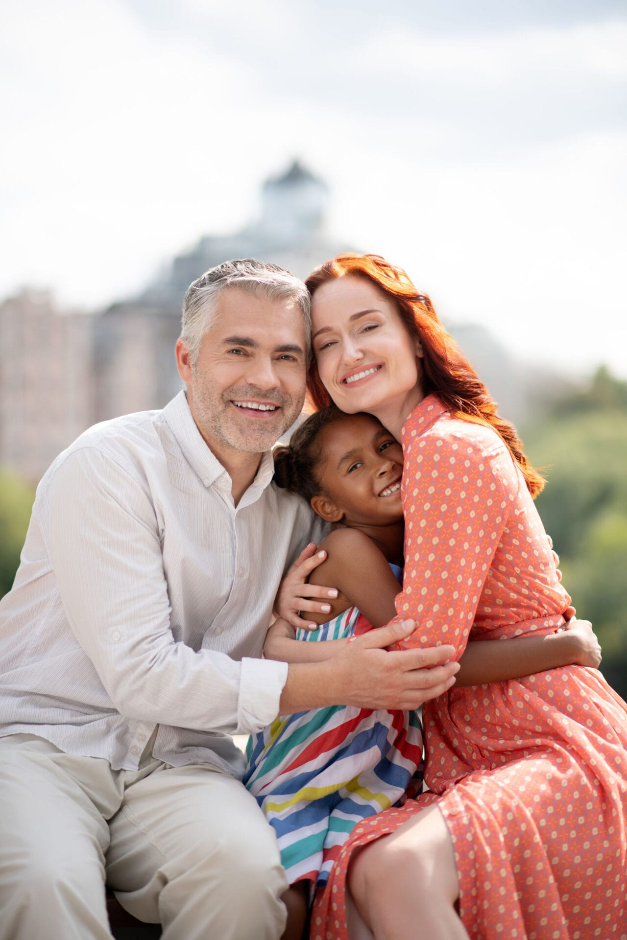 Mother and father. Foster mother and father hugging their cute happy daughter while spending day together